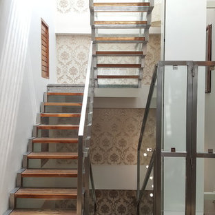 Inspiration for a transitional wooden u-shaped metal railing staircase remodel in Chennai with glass risers