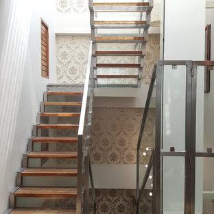 Imagen de escalera en U, clásica renovada, con escalones de madera, contrahuellas de vidrio y barandilla de metal