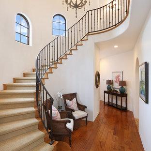 Пример оригинального дизайна интерьера: изогнутая лестница в средиземноморском стиле с деревянными ступенями и деревянными подступенками