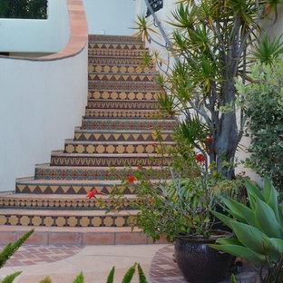 Ejemplo de escalera mediterránea, extra grande, con escalones con baldosas y contrahuellas con baldosas y/o azulejos