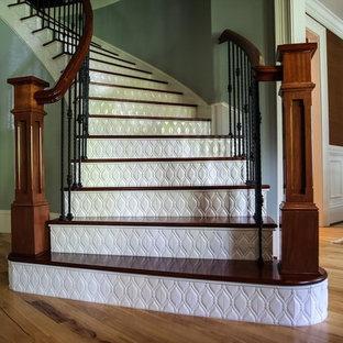Modelo de escalera curva, tradicional, grande, con escalones de madera y contrahuellas con baldosas y/o azulejos