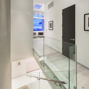 Réalisation d'un escalier flottant design avec des marches en bois, des contremarches en verre et un garde-corps en verre.