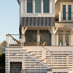 Example of a mid-sized beach style wooden u-shaped cable railing staircase design in New York with wooden risers