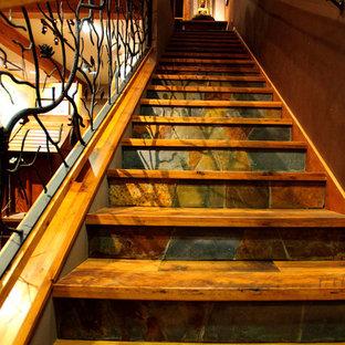 クリーブランドの中くらいの木のトラディショナルスタイルのおしゃれなかね折れ階段 (スレートの蹴込み板、金属の手すり) の写真