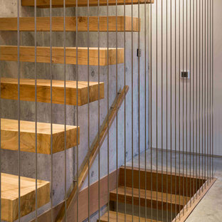 Photo of a large contemporary wood straight staircase in London with open risers.