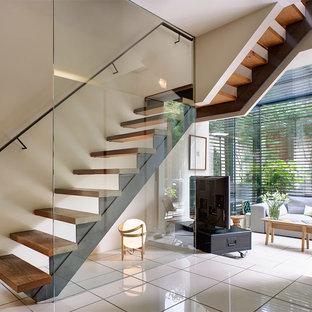 Modern inredning av en mellanstor svängd trappa i trä, med sättsteg i glas och räcke i metall