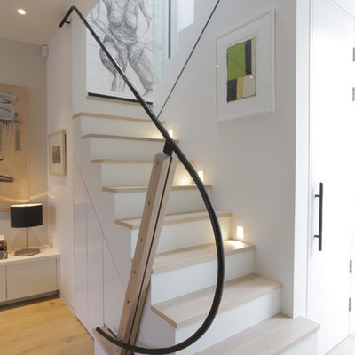 Inspiration for a mid-sized contemporary wooden u-shaped metal railing staircase remodel in London with painted risers