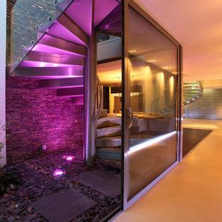 Esempio di una grande scala a chiocciola design con pedata in vetro, alzata in vetro e parapetto in metallo
