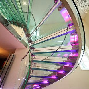Идея дизайна: большая винтовая лестница в современном стиле с стеклянными ступенями, стеклянными подступенками и металлическими перилами