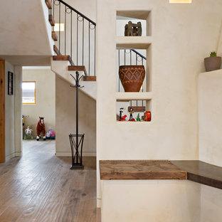 Cette photo montre un escalier flottant sud-ouest américain de taille moyenne avec des marches en bois, des contremarches en bois peint et un garde-corps en métal.