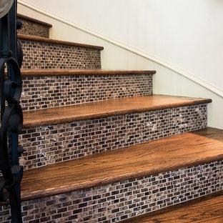 ダラスの中くらいの木の地中海スタイルのおしゃれなサーキュラー階段 (タイルの蹴込み板、金属の手すり) の写真