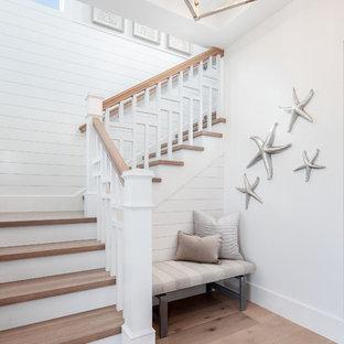 Aménagement d'un escalier bord de mer en L avec des marches en bois, des contremarches en bois peint et un garde-corps en bois.