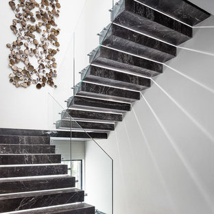 ロサンゼルスの大理石のモダンスタイルのおしゃれな折り返し階段 (大理石の蹴込み板、ガラスの手すり) の写真