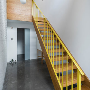 Design ideas for a contemporary wood straight metal railing staircase in London with open risers.