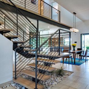 Immagine di una scala sospesa minimalista di medie dimensioni con pedata in legno, nessuna alzata e parapetto in metallo