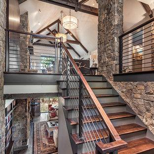 Diseño de escalera en U, rústica, grande, con escalones de madera, contrahuellas de madera pintada y barandilla de cable