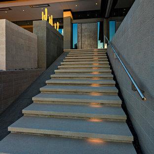Immagine di una grande scala a rampa dritta minimalista con pedata in cemento, alzata in cemento e parapetto in metallo