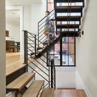 Ejemplo de escalera en U, clásica renovada, sin contrahuella, con escalones de madera y barandilla de metal