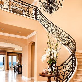 Diseño de escalera curva, mediterránea, grande, con escalones de travertino, contrahuellas de travertino y barandilla de metal