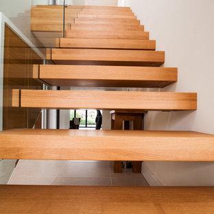 Foto de escalera recta, minimalista, de tamaño medio, con escalones de madera, contrahuellas de madera y barandilla de vidrio