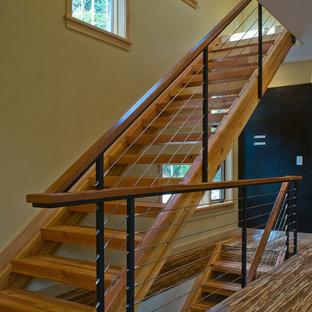 Imagen de escalera recta, actual, grande, sin contrahuella, con escalones de madera y barandilla de cable
