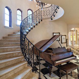Bild på en medelhavsstil svängd trappa i marmor, med sättsteg i marmor och räcke i metall