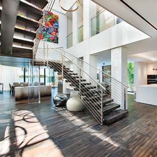 This is an example of an expansive contemporary wood curved wire cable railing staircase in Miami with open risers.