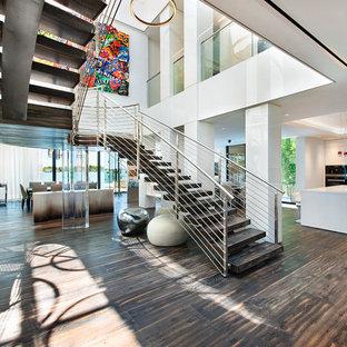 Foto de escalera curva, actual, extra grande, sin contrahuella, con escalones de madera y barandilla de cable