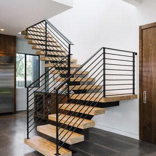 Foto de escalera en L, minimalista, grande, sin contrahuella, con escalones de madera y barandilla de metal
