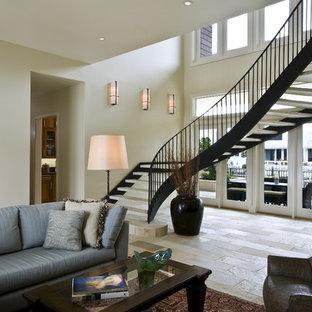 Foto de escalera curva, actual, grande, sin contrahuella, con escalones de piedra caliza y barandilla de metal