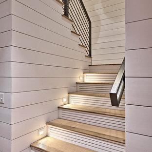 """Immagine di una grande scala a """"U"""" tradizionale con pedata in legno, alzata in legno verniciato e parapetto in metallo"""