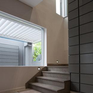 Ejemplo de escalera en L, minimalista, grande, con escalones de travertino y contrahuellas de travertino