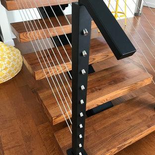 Idee per una scala a rampa dritta design di medie dimensioni con pedata in legno, nessuna alzata e parapetto in cavi