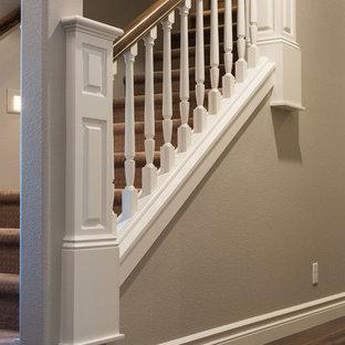 シアトルの広いカーペット敷きのコンテンポラリースタイルのおしゃれな直階段 (カーペット張りの蹴込み板、木材の手すり) の写真
