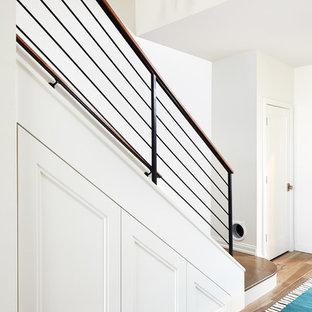 Modelo de escalera recta, moderna, pequeña, con escalones de madera, barandilla de metal y contrahuellas de madera pintada