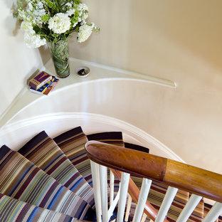 Foto de escalera curva, ecléctica, con escalones enmoquetados