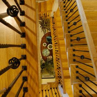 ボストンの広い木のトラディショナルスタイルのおしゃれな折り返し階段 (木の蹴込み板、金属の手すり) の写真