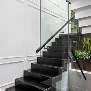 シドニーのコンテンポラリースタイルのおしゃれな折り返し階段 (ガラスの手すり、パネル壁) の写真