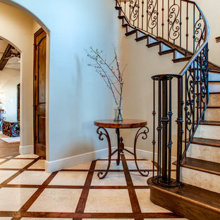 Imagen de escalera curva, clásica, grande, con escalones de madera y contrahuellas de metal