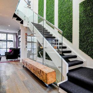Diseño de escalera suspendida, contemporánea, de tamaño medio, sin contrahuella, con escalones enmoquetados y barandilla de vidrio