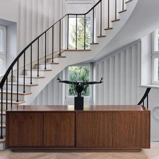 На фото: изогнутые лестницы в стиле модернизм с деревянными ступенями, крашенными деревянными подступенками и металлическими перилами