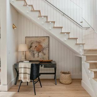Imagen de escalera en L y panelado, clásica renovada, con escalones de madera, contrahuellas de madera, barandilla de vidrio y panelado
