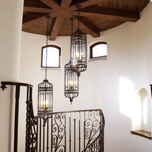 Ejemplo de escalera curva, mediterránea, grande, con escalones de madera y contrahuellas de madera