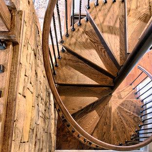 Idee per una scala a chiocciola stile rurale di medie dimensioni con pedata in legno e alzata in metallo