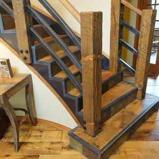 На фото: большая изогнутая лестница в стиле рустика с деревянными ступенями, подступенками из сланца и деревянными перилами с