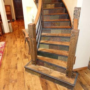 Esempio di una grande scala curva rustica con pedata in legno, alzata in ardesia e parapetto in legno