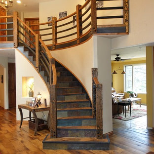 Foto de escalera curva, rústica, grande, con escalones de madera, contrahuellas de pizarra y barandilla de madera