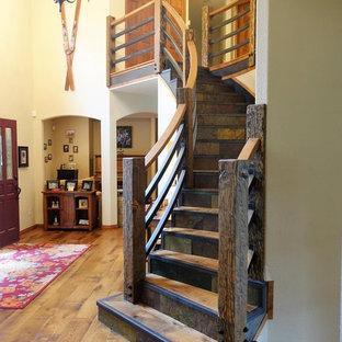 Modelo de escalera curva, rústica, grande, con escalones de madera, contrahuellas de pizarra y barandilla de madera