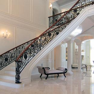 Foto de escalera curva, tradicional, grande, con escalones de mármol, contrahuellas de mármol y barandilla de metal