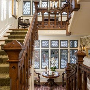 На фото: большая п-образная лестница в викторианском стиле с деревянными ступенями